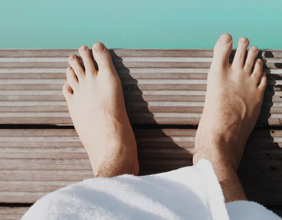 Bare feet on decking near water