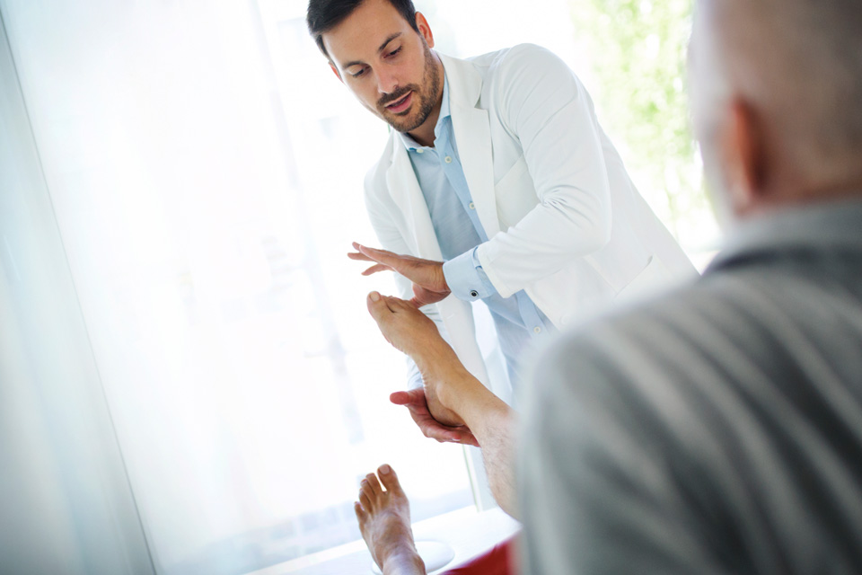 Male doctor examining patient's foot