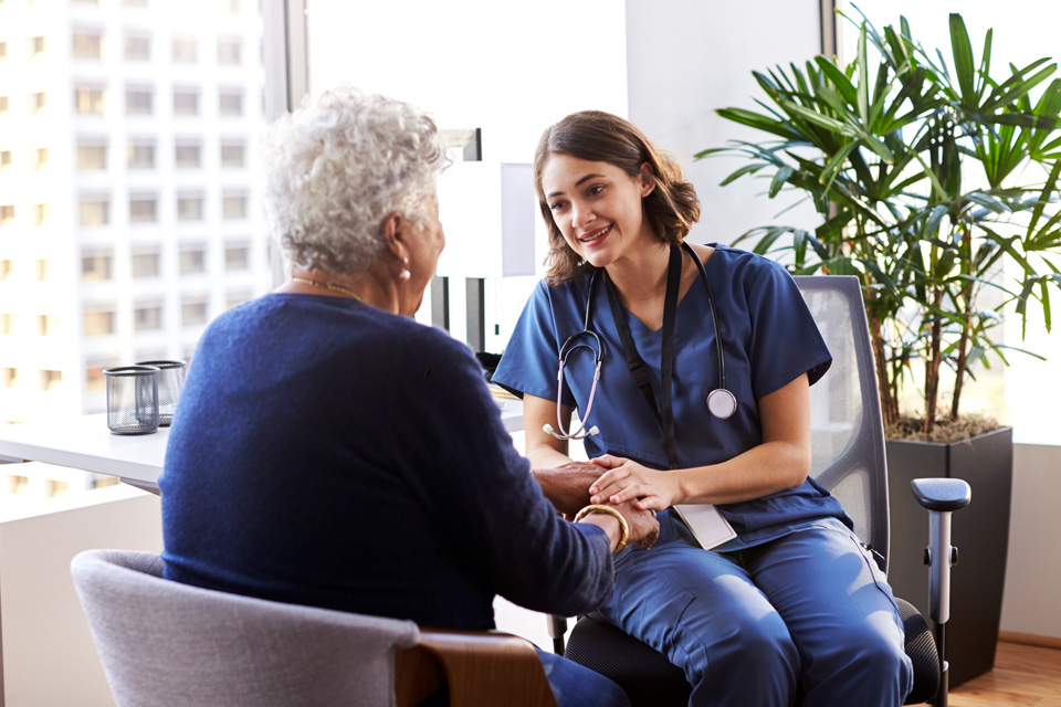 Female doctor talking with older patient