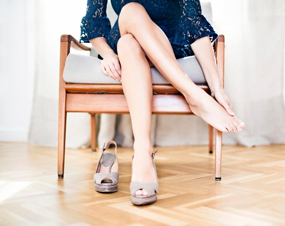 Woman in blue dress sitting rubbing foot